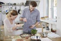 Couple preparing pizza in kitchen — Stock Photo