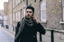 Jovem homem casual andando na rua usando telefone celular — Fotografia de Stock