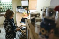 Woman cooking on gas stove in her kitchen — Stock Photo