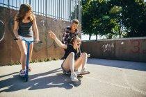 Tre amici adolescenti giocosi che si divertono con scooter e skateboard — Foto stock