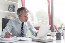 Reifer Mann arbeiten im Büro mit laptop — Stockfoto
