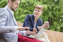 Two young business people sitting on wooden bench with laptop and coffee to go — Stock Photo