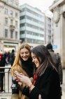 Junge Frauen mit Smartphone auf Stadtstraße in London, Vereinigtes Königreich — Stockfoto
