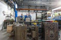 Three men in factory talking at metal workpiece — Stock Photo
