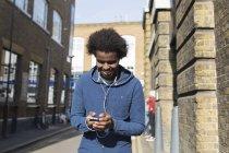 Молода людина, прослуховування музики з мобільного телефону на міських вулиць — стокове фото