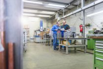 Deux hommes en usine à une pièce métallique — Photo de stock