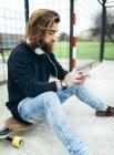 Jeune skateur barbu avec smartphone et écouteurs — Photo de stock