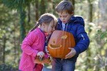 Хлопчик і дівчинка вивчення Хеллоуїна гарбуза в лісі — стокове фото