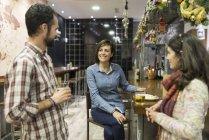 Three smiling friends talking in bar — Stock Photo