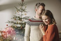 Happy couple hugging in front of Christmas tree — Stock Photo
