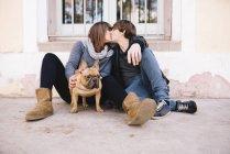 Молодая пара с французским бульдогом сидит на земле и целуется — стоковое фото