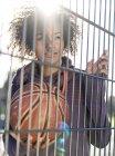 Портрет молодой женщины с баскетболом, стоящей за забором — стоковое фото