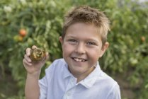 Retrato de niño sosteniendo tomate con mordida faltante - foto de stock