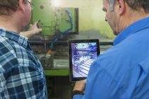 Двоє чоловіків у заводу з цифровий планшетний в машині — стокове фото