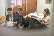 Двоє чоловіків та жінка читання документи в офісі — стокове фото