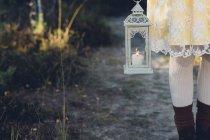 Старомодный стиль женщина, держащая шторм лампа, частичным видом — стоковое фото