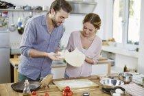 Couple préparant la pâte à pizza dans la cuisine — Photo de stock