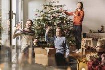 Famiglia che decora l'albero di Natale e sventolando fuori dalla finestra — Foto stock
