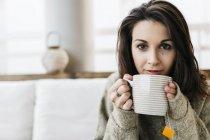 Портрет женщины с чашкой чая, смотрящей в камеру — стоковое фото