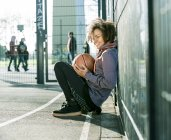 Young woman with basketball crouching on a playing field — Stock Photo