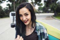 Portrait of smiling young woman with longboard behind her back — Stock Photo