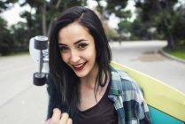 Retrato de mulher jovem sorridente com longboard nas costas — Fotografia de Stock