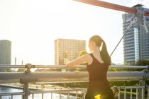 Young athlete standing on bridge looking at view — Stock Photo