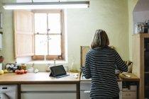 Rückansicht einer Frau, die in ihrer Küche auf einem Gasherd kocht — Stockfoto
