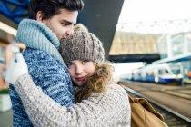 Couple embracing on station platform — Stock Photo