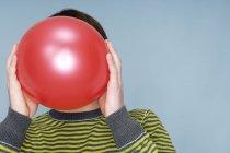 Мальчик-подросток прячет лицо за красным шариком на синем фоне — стоковое фото