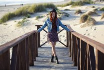 Portrait of young redheaded woman standing on boardwalk at the beach — Stock Photo