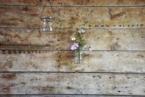 Typical decoration with flowers hanging in glass on wooden wall — Stock Photo
