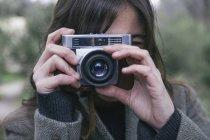 Женщина фотографируется с аналоговой камерой — стоковое фото