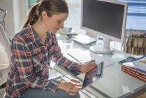 Giovane donna alla scrivania in ufficio guardando tablet digitale — Foto stock