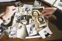 Руки пожилой пары с их старыми фотографиями — стоковое фото