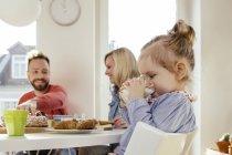 Little girl drinking milk at breakfast table — Stock Photo