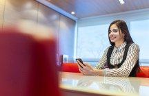 Retrato de uma mulher de negócios sorridente sentada em uma sala de conferências com seu smartphone — Fotografia de Stock