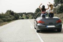 Женщины веселятся в кабриолете на проселочной дороге — стоковое фото