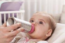 Девочка пить из бутылки — стоковое фото