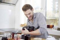 Jeune homme avec des pots de confiture dans la cuisine — Photo de stock