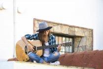 Junge Frau spielt draußen Gitarre — Stockfoto