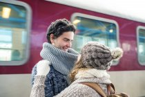 Couple embracing in front of train — Stock Photo