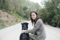Портрет улыбающейся женщины с собакой в природе — стоковое фото