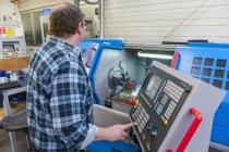 Man in factory operating machine — Stock Photo