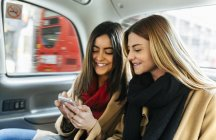 Two young women using smart phone in black cab, London, UK — Stock Photo