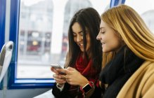 Two young women using smart phone on the bus, London, UK — Stock Photo