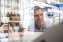 Man and woman looking at transparent touchscreen device — Stock Photo
