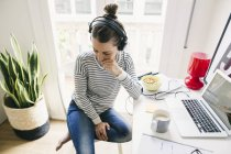 Woman sitting at table wearing headphones — Stock Photo