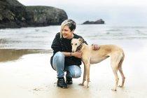 Щасливі молодої жінки з її greyhound на пляжі — стокове фото