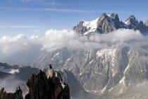 France, Ecrins Massif, Aiguille Noire de Peuterey and Mont Pelvoux, cheering mountaineer on summit — Stock Photo